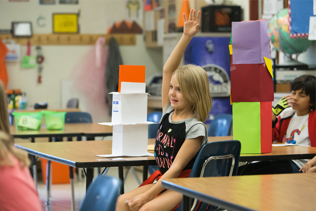 PHoto of Child in Classroom Raising her Hand