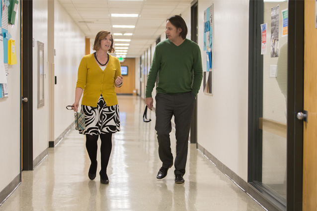 Photo of two people talking in hallway