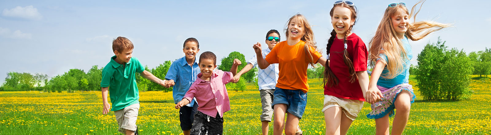 Group of kids running through a field on a sunny day